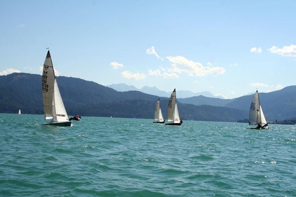 Auf dem Bild ist sind mehrere Segelboote zu sehen, die bei perfektem Wind und kristallklare Bergwasser über den Tegernsee segeln.