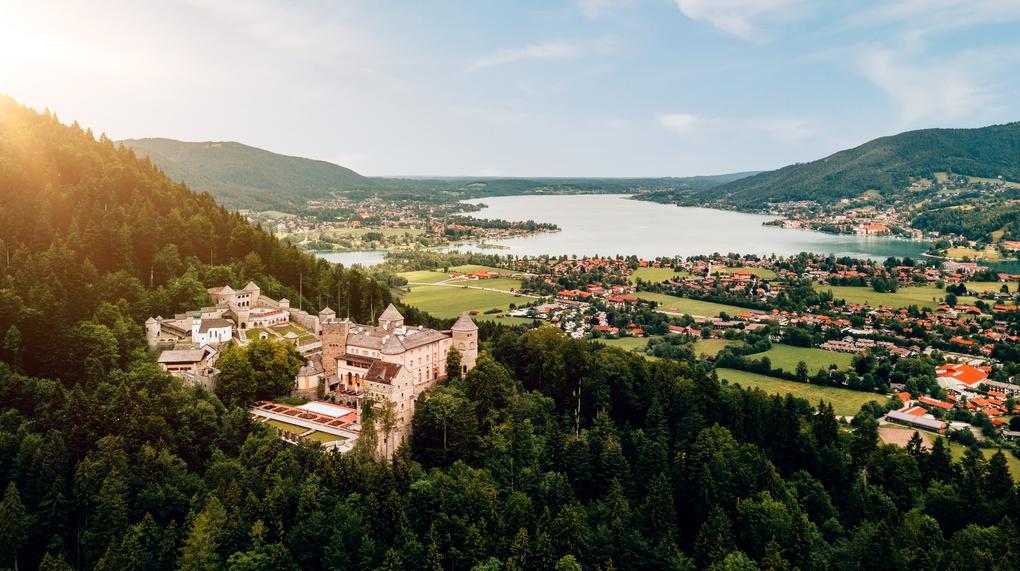 Auf dem Bild ist im Vordergrund das traumhafte Schloss Ringberg am Tegernsee zu sehen, das durch minimale Sonnenstrahlen angestrahlt wird. Im Hintergrund sieht man die den ganzen Tegernsee in seiner vollen bracht.
