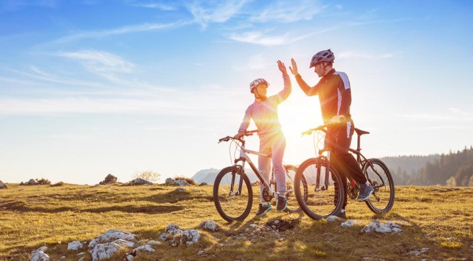 Auf dem Bild sind ein weiblicher und männlicher Fahrradfahrer zu sehen, die sich nach erfolgreichem Rad-Tour um de Tegernsee abklatschen.